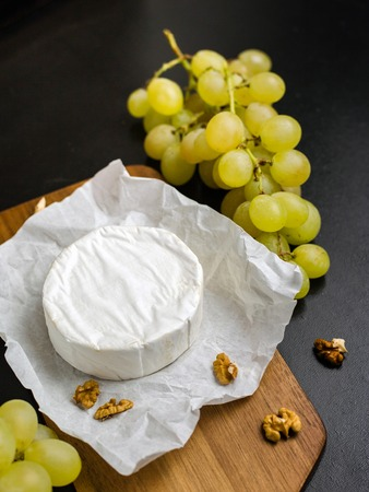 Soft cheese. Camembert and grapes on a wood with nuts