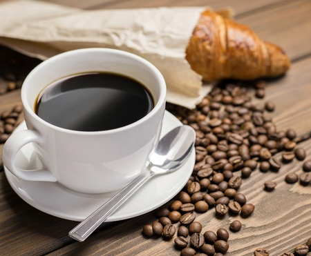Coffee cup, beans and croissant in paper packaging on wooden background on the table. Perfect breakfast in the morning. Rustic style
