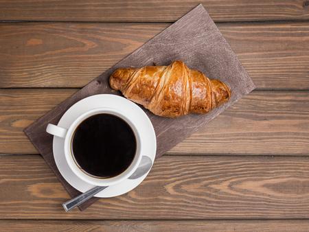 Kaffeetasse und Croissant auf Holzuntergrund auf dem Tisch. Perfektes Frühstück am Morgen. Rustikaler Stil, Draufsicht
