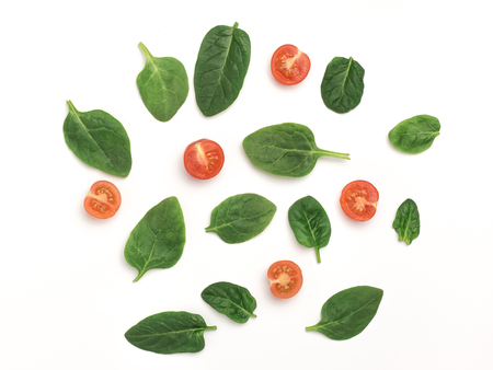 spinach and slices of baby tomatoes on a white background, top view with copy space, mock up