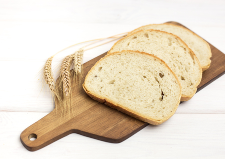 fresh sliced bread and wheat on wooden cutting board on white wooden table