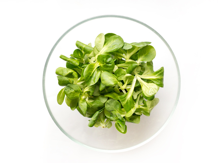 Fresh green Corn salad leaves or lambs lettuce in bowl. Top view, lambs lettuce isolated on white background