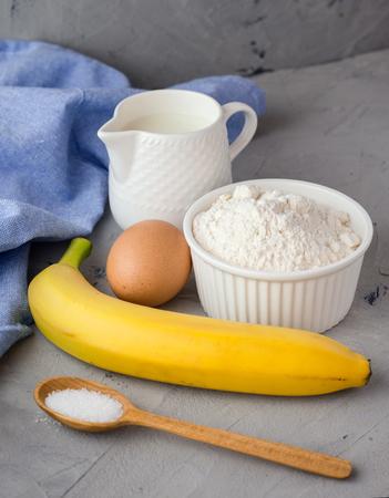 The ingredients for the banana cake on gray background. Wooden Spoon, Banana, Eggs, Milk 版權商用圖片