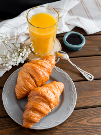 delicious breakfast with croissants, flowers and juice, good morning. Glass of refreshing orange fruit juice Stock Photo