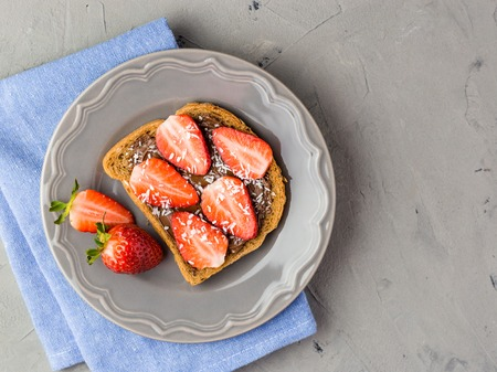 Toast with chocolate and strawberry, Single sandwich with chocolate cheese on white plate, top view