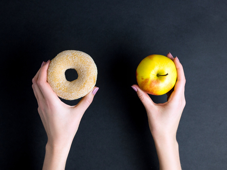 hands hold donut and apple on dark background