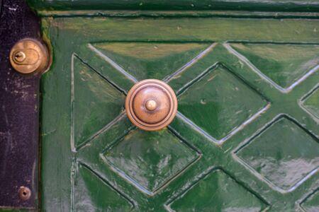 Antique door knob in old town. Classic brass door knob on green door vintage style