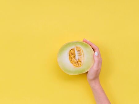 Womans hand hold a cut melon in half. Ripe melon cut in half on a bright yellow background.