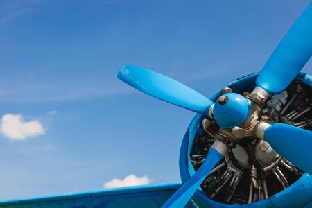Close up abstract of a vintage airplane propeller engine against blue sky, closeup. Travel concept