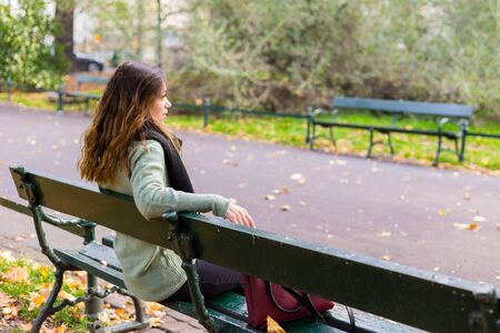 Beautiful girl sitting on a bench, sunny autumn day in the park, relaxing, after work business woman