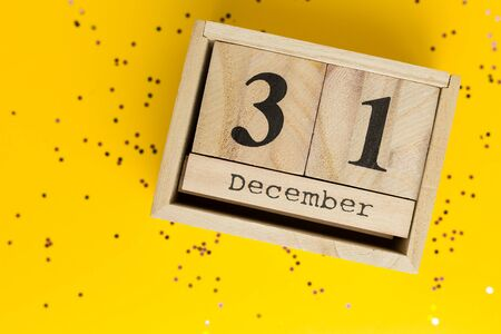 New year Date On Calendar. December 31. Yellow background with multicolored confetti. Flat lay style, top view. Winter time.
