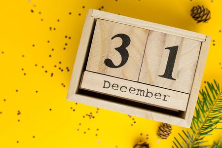 New year Date On Calendar. December 31. Yellow background with multicolored confetti, pine branches, cones. Flat lay style, top view. Winter time. Imagens - 134836005