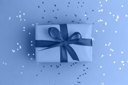 Present for Christmas or a birthday. Classic Blue color of the year. Blue trend background with multicolored confetti. Flat lay style. Banque d'images - 138459561