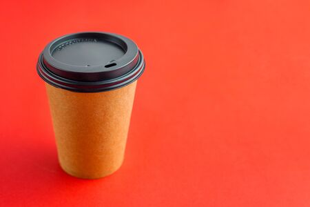 Paper coffee cup on red background with copy space.