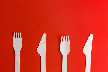 Wooden disposable forks, knifes on red background, recycling and eco friendly concept.