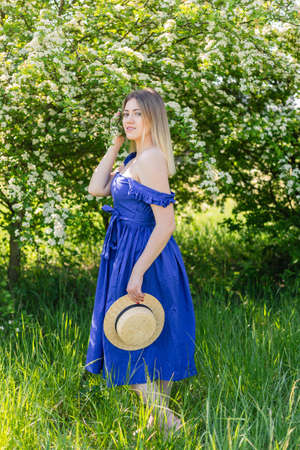 Portrait of beautiful hipster woman in blooming bush with white flowers of spirea. Copy space. Stylish blonde woman in blue dress with straw hat in garden