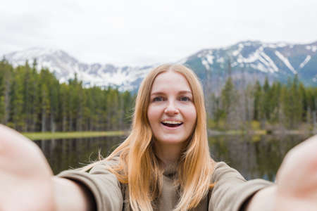 The girl tourist taking selfie in the mountain lake. Looking at camera and smile. Travel and active life concept. Outdoors Foto de archivo
