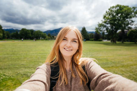 Beautiful young hipster woman taking selfie in the public park. Looking at camera and smile. Travel and active life concept. Outdoors