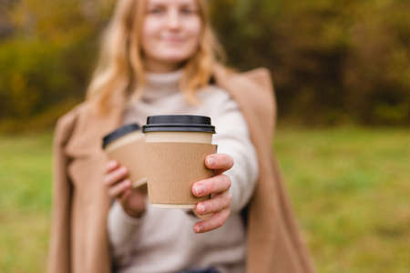 Woman holds two paper coffee cups. Take away or delivery concept. Copy space. Autumn lifestyle. Place for your text or logo on mug, mockup Banco de Imagens