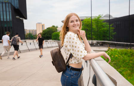 Beautiful young woman posing at the city street background. Girl relax in a sunny day. Travel and active life concept. Banco de Imagens