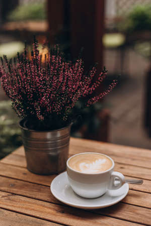 One cup of cappuccino with latte art on wooden table, white ceramic cup, place for text. Terrace with a table in a cafe or at home