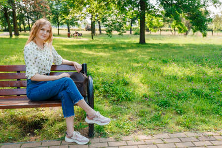 The beautiful young woman sits on a bench