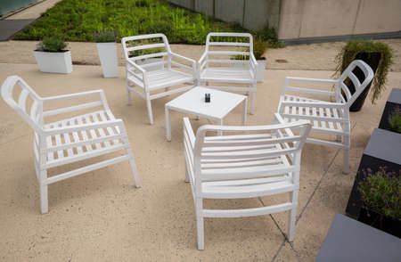 Outdoor furniture in garden, white chairs with table in cafe