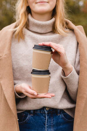 Woman holds two paper coffee cups. Take away or delivery concept. Copy space. Autumn lifestyle. Place for your text or logo on mug Banco de Imagens