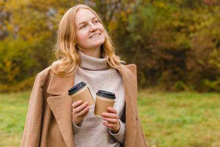 Woman holds two paper coffee cups. Take away or delivery concept. Copy space. Autumn lifestyle.