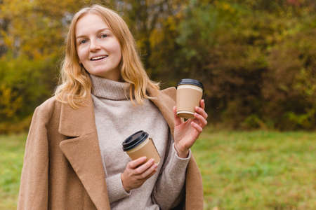 Woman holds two paper coffee cups. Take away or delivery concept. Autumn lifestyle. Place for your text or logo on mug, mockup