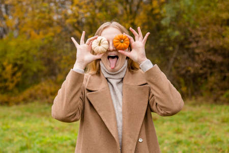The girl covers part of her face with an orange and white pumpkins. Harvest concept. Copy space. Autumn lifestyle. Smiling Woman being playful covering her eyes with pumpkins