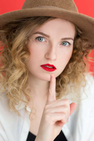 Young woman with green eyes wearing white shirt over red background pointing finger up. Shh. Women's secrets. Portrait of female with finger in mouth.