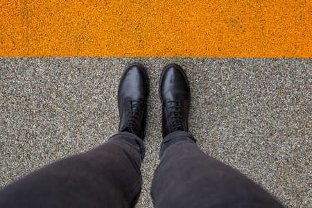 Black shoes standing on the asphalt concrete floor with orange line. Feet shoes walking in outdoor. Youth selphie hipster