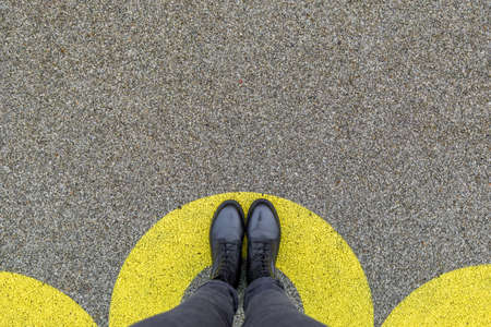 Black shoes standing in yellow circle on the asphalt concrete floor. Comfort zone or frame concept. Feet standing inside comfort zone
