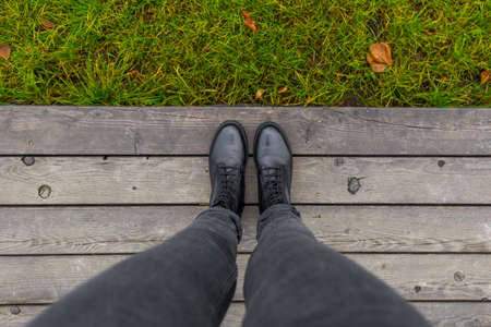 Black shoes standing on the wooden pier. Feet shoes walking in outdoor. Youth selphie hipster