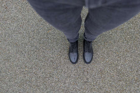 Black shoes standing on the asphalt concrete floor. Feet shoes walking in outdoor. Youth selphie hipster