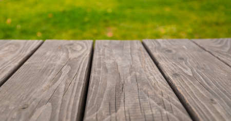 Empty wooden table on bright green abstract blurred summer background Banco de Imagens
