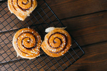 Cinnabons won a wire rack on the table. Food concept. Homemade sweet pastries