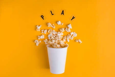 Paper cup with popcorn and text PLAY on yellow background. Flat lay banner, To go to the cinema. I like watching films.