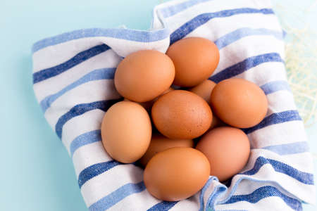 Brown Chicken eggs with rustic cloth on the bright blue background. Farm natural products, food or Easter concept. Top view, flat lay