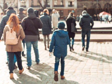 Blurred background. Blurred people walking through a city street. The photo is made out of focus, no faces are recognisable