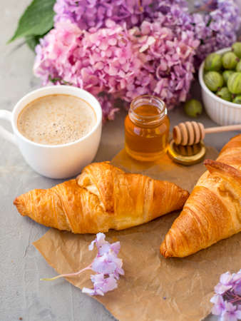 Breakfast served with coffee, croissants, natural honey jar and flowers