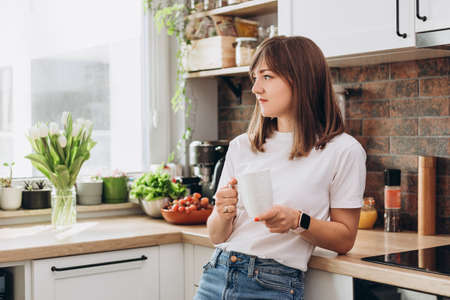 Close up woman in white t-shirt drinking coffee or tea in kitchen at home. Early breakfast in the morning, rest time