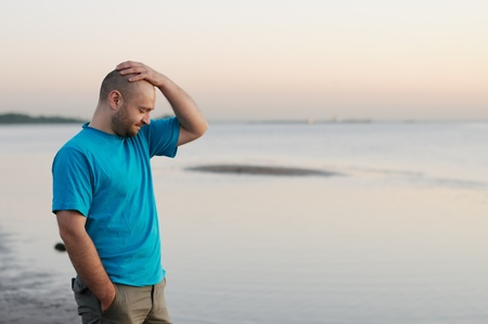 Depression - Bald man standing by the sea photo