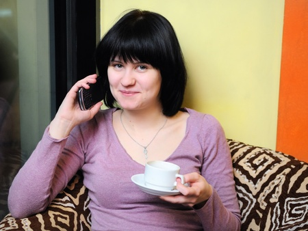 Young girl holding coffee and using her mobile phone  Stock Photo - 9960219