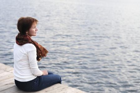여자는 물에 의해 나무 보드에 sittng된다