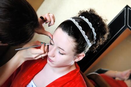 primp: Giovane bella sposa che applica trucco di cerimonia nuziale da make-up artist Archivio Fotografico