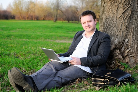 Businessman with laptop working under a tree Stock Photo - 9955667