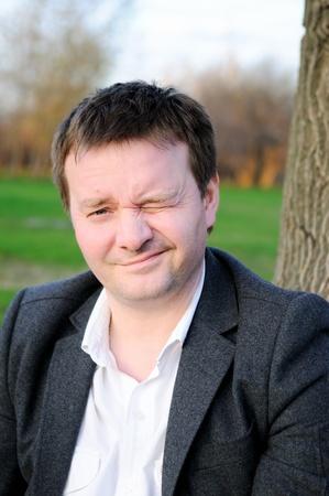 Funny man winking, outdoors portrait Stock Photo - 9955668