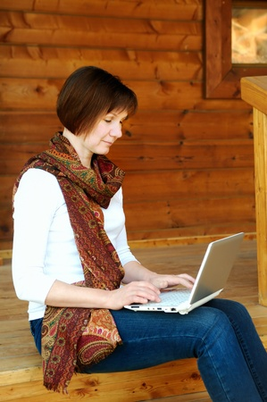 Woman with laptop sitting on wooden porch  Stock Photo